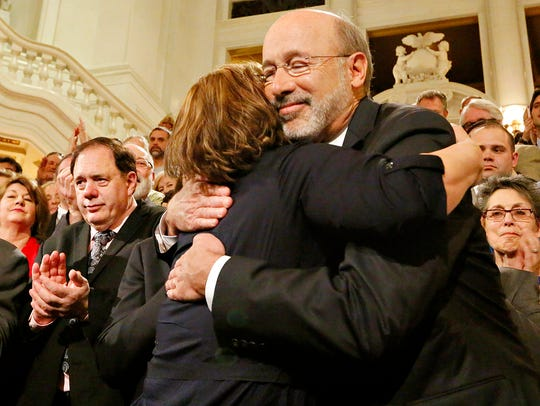 Lolly Bentch, of Harrisburg, hugs Gov. Tom Wolf before