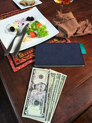 In this photo illustration, a tip for the waiter is left on the table after dining at a restaurant.