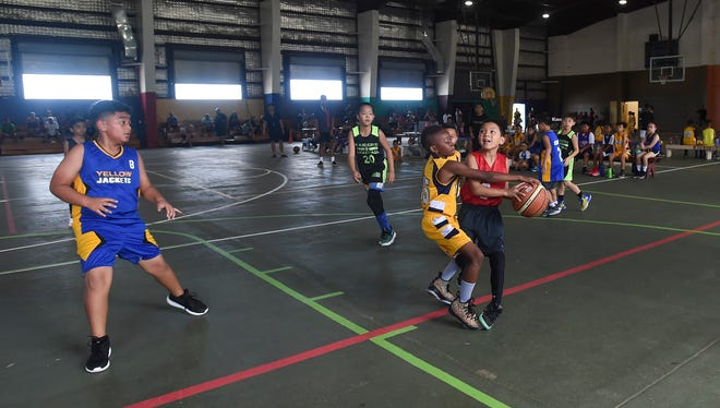 In this file photo, Raiders player Addison de los Santos is guarded by a Yellow Jackets defender during their Guam Youth Basketball Association Drug Free League game at Astumbo Gym on June 9, 2018.