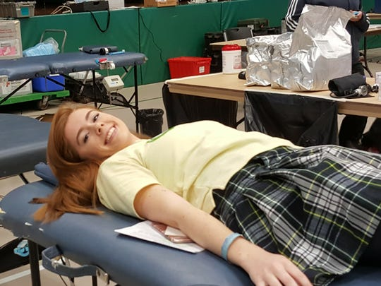 Courtney Mosley of Millville, a junior at Our Lady of Mercy Academy, donates blood for the first time during the academy's annual blood drive.