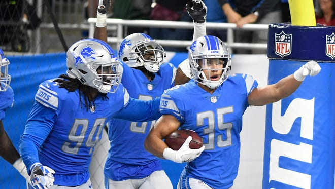 Lions safety Miles Killebrew (35) celebrates his 35-yard interception return for a touchdown late in the fourth quarter of the Lions' 35-23 win over the Cardinals at Ford Field on Sept. 10, 2017.