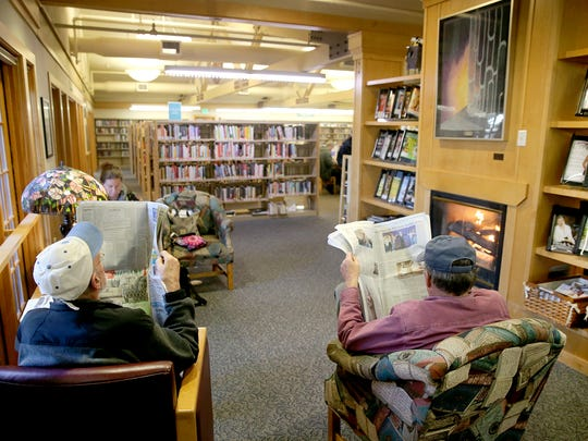 File photo — Poulsbo Library patrons read newspapers by the fireplace.