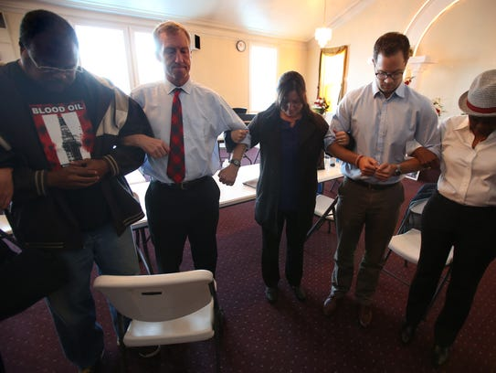 Tom Steyer, middle, prays with his staff and neighborhood