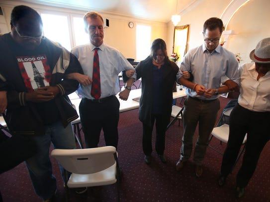 Tom Steyer, middle, prays with his staff and neighborhood