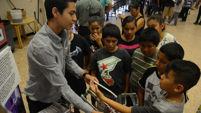 Enrique Gamboa shows elementary students a robotic arm he made during a special presentation for ASES, migrant, English learner and special education students in Coachella Valley Unified School District.