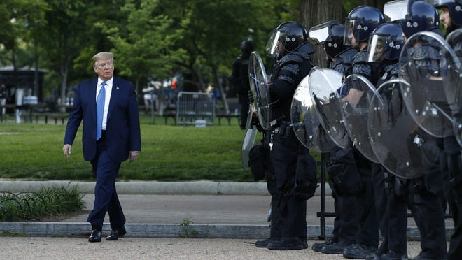 President Donald Trump walks past police in Lafayette Park on June 1 after visiting outside St. John's Church across from the White House in Washington.