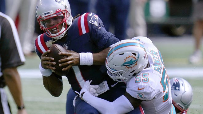 Patriots quarterback Cam Newton absorbs a hit from Dolphins linebacker Jerome Baker during the first half of Sunday's season opener in Foxborough, Mass. Newton rushed 15 times for 75 yards and two touchdowns, all team highs, in the Patriots' 21-11 win.