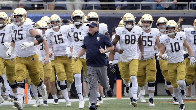 FILE - In this Dec. 28, 2019, file photo, Notre Dame head coach Brian Kelly, center, runs onto the field with his players before the Camping World Bowl NCAA college football game against Iowa State in Orlando, Fla. The Atlantic Coast Conference and Notre Dame are considering whether the Fighting Irish will give up their treasured football independence for the 2020 season play as a member of the league.