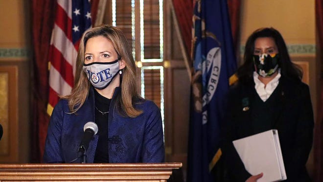 In this Wednesday, Oct. 28, 2020, file photo, provided by the Michigan Office of the Governor, Michigan Secretary of State Jocelyn Benson addresses the state in Lansing, accompanied by Gov. Gretchen Whitmer, background.