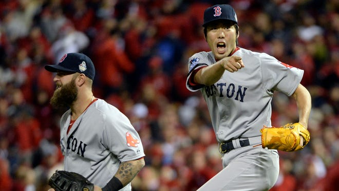 Red Sox relief pitcher Koji Uehara celebrates with first baseman Mike Napoli after beating the St. Louis Cardinals at Busch Stadium.