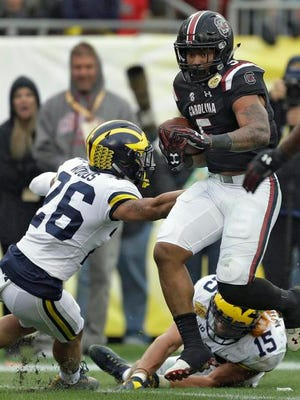 South Carolina running back Rico Dowdle (5) runs over Michigan defensive back J'Marick Woods (26) and defensive lineman Chase Winovich (15) on a 7-yard touchdown run during the second half of the Outback Bowl NCAA college football game Monday.
