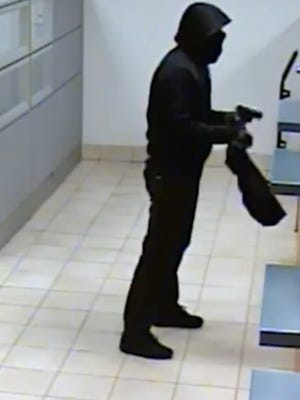 Authorities allege an Atlantic County man is the armed robber seen in this surveillance photo from an Evesham bank robbery.
