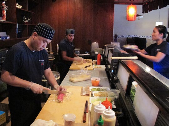 Donny Sam, left, creates a sushi roll at Hibachi of