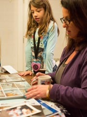 Audrey Stepp, 8, looks at family photos of her brother