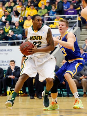 North Dakota State University's Kory Brown (22) scores past Reed Tellinghuisen (23) of South Dakota State University during the Saturday, January 16, 2016 game at Scheels Arena in Fargo, N.D.