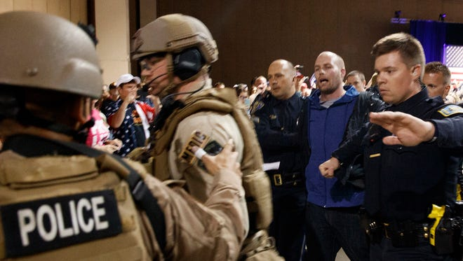 Law enforcement officers escort Austyn Crites, 33, of Reno, Nev., out of a Donald Trump rally Nov. 5, 2016, moments after theh GOP presidential nominee was rushed offstage by Secret Service agents during a campaign rally in Reno.