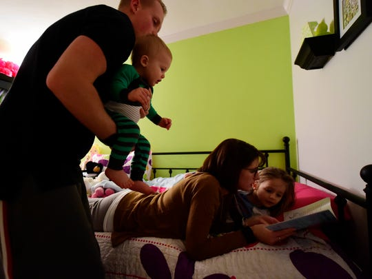 Chris Doemland holds his son, 11-month-old Sammy,  as his wife Erin Doemland reads to their daughter Amelia, 3, at their home in West Manchester Township. When training gets tough, Doemland said he thinks about his motivation for getting healthy -- his family.