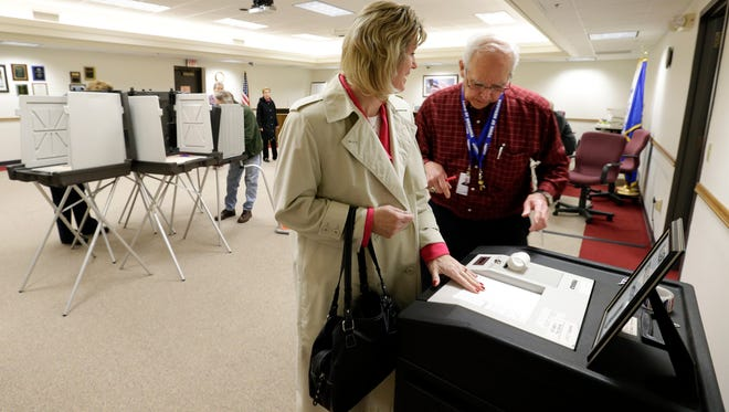 Mary Pfeiffer is the first person to cast her vote as Jim Labre, chief inspector, confirms that the voting machine is working properly at the Town of Menasha Municipal Complex Tuesday, April 7, 2015, in the Town of Menasha, Wis. Dan Powers/Post-Crescent Media