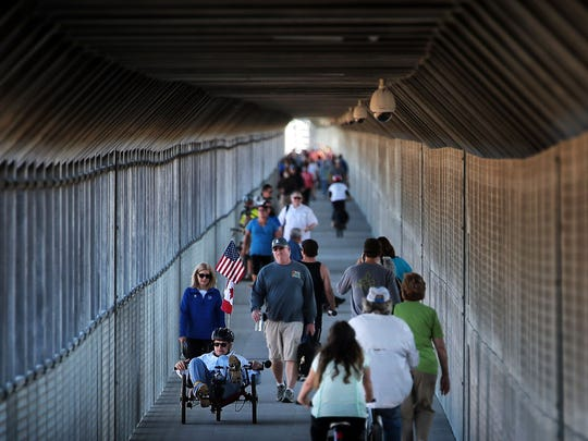 Bikers and pedestrians traverse the slow incline on the Arkansas side of the Big River Crossing on the Harahan Bridge. The new crossing, which opened with much fanfare on Saturday allows cyclists and walkers to cross the river alongside Union Pacific Railroad freight trains.
