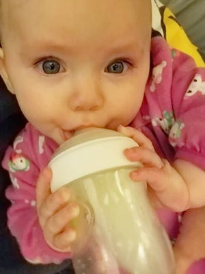 Five-month-old Blair Walker nurses breast milk from a bottle after her mother had to stop nursing due to new medications.