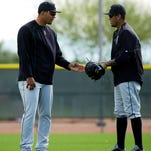 Seattle Mariners' Felix Hernandez, right, checks out a glove belonging to Taijuan Walker during spring training baseball practice Tuesday, Feb. 24, 2015, in Peoria, Ariz.