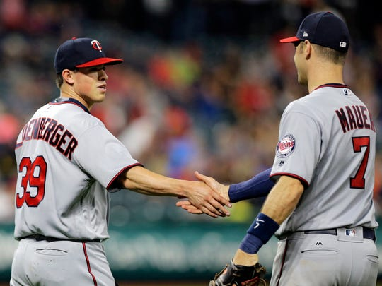 Minnesota Twins relief pitcher Trevor Hildenberger, left, is congratulated by Joe Mauer after the Twins defeated the Cleveland Indians 5-0 in a baseball game, Friday, June 23, 2017, in Cleveland. (AP Photo/Tony Dejak)