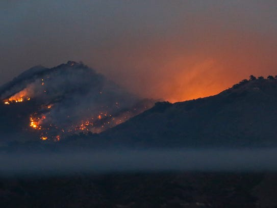 The 3,016 foot tall Los Coches Mountain burns during