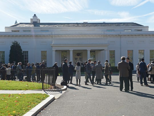 People gather outside the West Wing of the White House