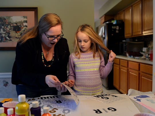 "From left, Kelly Breen reacts as she points out a letter to her daughter, Abi Breen, 6 both of Novi, as they decorate her sign to read ""Girl Power"" on Sunday, Jan. 8, 2017 at a sign-making party at a home in Novi. The women made protest signs for the upcoming Women's March on Washington."