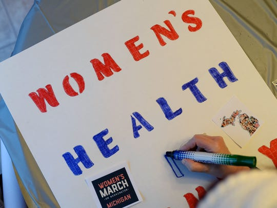 "Tali Wendrow, of West Bloomfield, colors in letters on her sign to read ""Women's Health is Family Health"" on Sunday, Jan. 8, 2017 at a sign-making party at a home in Novi. The women made protest signs for the upcoming Women's March on Washington."