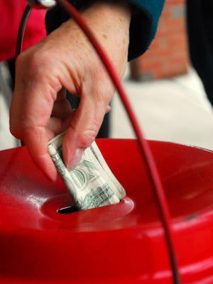 Barbara Shauck, from Pataskala, drops money into a Salvation Army collection kettle in 2008, outside the Ross Granville IGA.