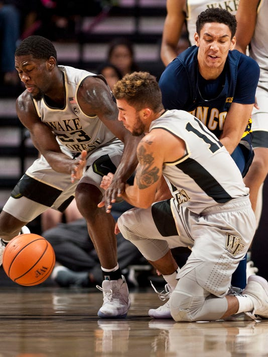 Wake Forest's Chaundee Brown (23) and Mitchell Wilbekin battle UNC Greensboro's Kyrin Galloway vie for a loose ball during the first half of an NCAA college basketball game, Friday, Nov. 24, 2017, in Winston-Salem, N.C. (Walt Unks/Winston-Salem Journal via AP)