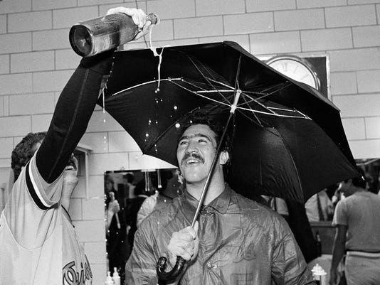 FILE - In this Sept. 25, 1983, file photo, Baltimore Orioles pitcher Sammy Stewart, right, uses an umbrella to keep dry as teammate Bill Swaggerty pours a beverage during their victory celebration after defeating the Milwaukee Brewers to win the American League Eastern Division title in Milwaukee, Wis. Stewart, who helped the Orioles win the 1983 World Series before falling into a life of drug addiction and arrests, has died. He was 63. The Henderson County Sheriff's Office said Stewart was found dead Friday, March 2, 2018, at a residence. No cause for his death had been determined as of Sunday. (AP Photo/Tom Lynn, File)