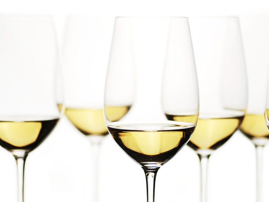 Crystal glasses of white wine on white background
