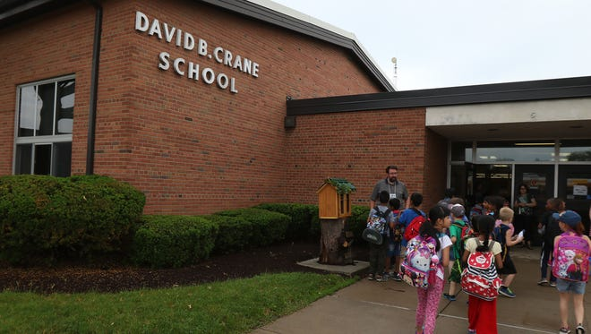 Students enter Crane Elementary School at the start of the day.