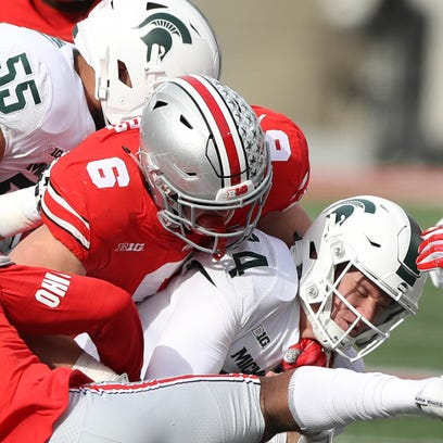 Michigan State's Brian Lewerke is tackled by Ohio State's