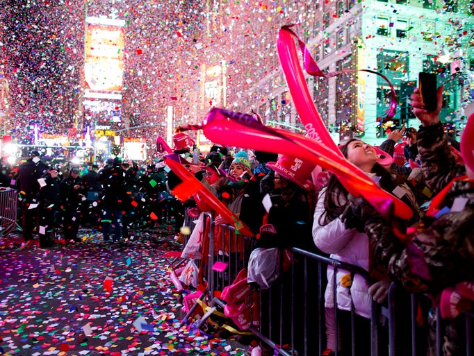Revelers are engulfed by confetti in New York City's