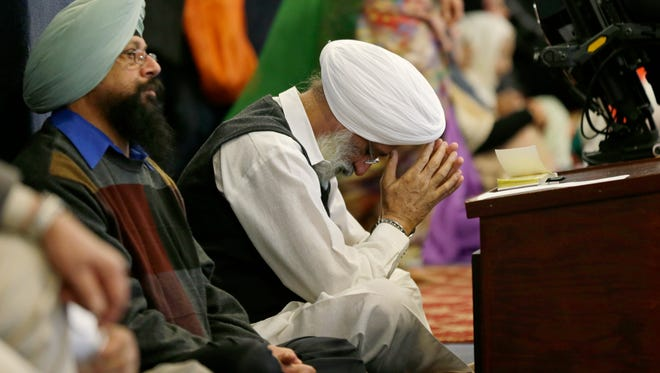 """A man bows his head as he attends Sunday services at a Sikh temple in Renton, Wash., on March 5, 2017, days after a local Sikh man was shot by a gunman who said """"go back to your own country."""""""