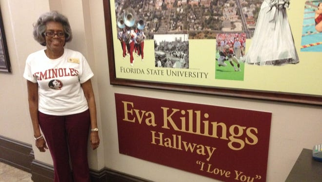 Eva Killings, who is known by current and former Florida State students, stands beside  tribute in her honor from a South Florida business executive.