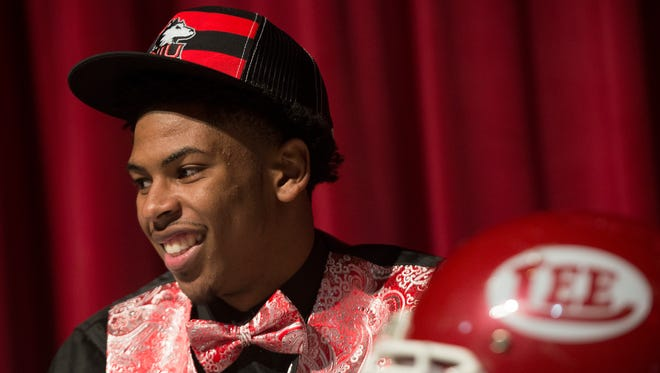 Lee football player Marquis Howard smiles after putting on his Northern Illinois hat after signing with them on Wednesday February 4, 2015 at Lee High School in Montgomery, Ala.