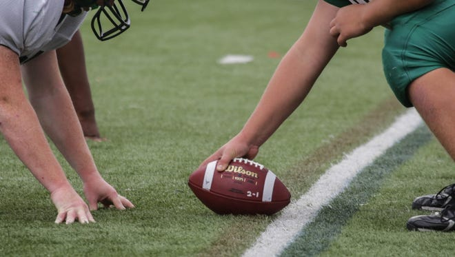 Varsity high school football players prepare to snap the ball during practice.