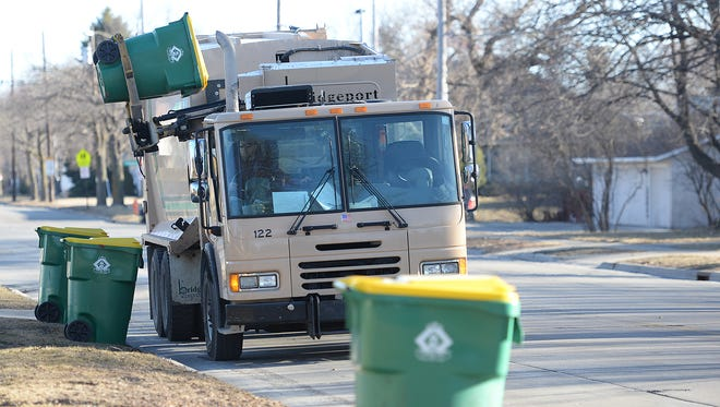 A Green Bay trash collection truck works on a row of bins on South Fisk Street on the city's west side on Tuesday.
