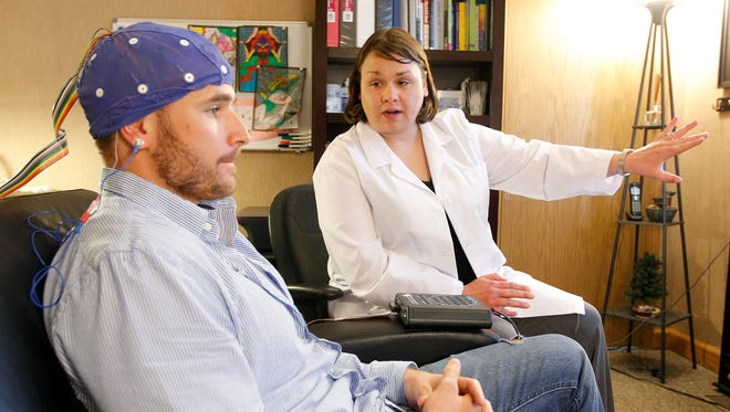 Amy Putney explains a quantitative electroencephalography test to Nic Zrostlik, who has dyslexia, at Brain Matters in Waterloo in May 2013.