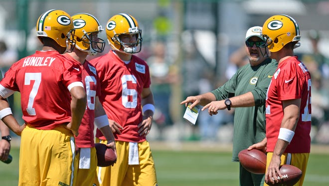Green Bay Packers quarterbacks Brett Hundley (7), left, Scott Tolzien (16), Matt Blanchard (6) and Aaron Rodgers (12) talk with coach Alex Van Pelt during minicamp at Clarke Hinkle Field June 16, 2015.