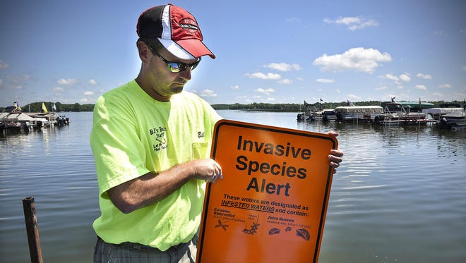 BJ's Bait & Tackle owner Bill Hohenstein holds a sign given to him recently by the DNR to post near his boat launch on Clearwater Lake near Annandale. Zebra mussels were recently discovered in the lake.