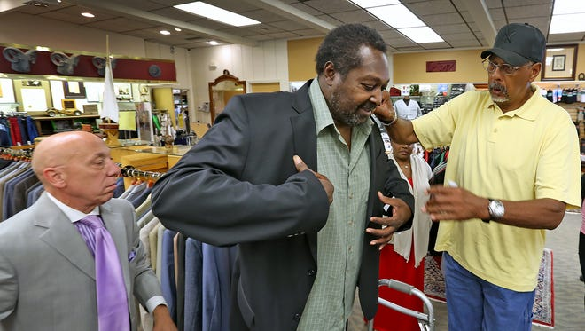 Former ABA basketball player Charlie Jordan, center, gets fitted for a new suit at the Style Store for the Big & Tall, Friday, August 21, 2015, with the help of store sales manager Steve Hoaglin, left, and former player Mel Daniels.  The suit and other items were bought for Jordan through the Dropping Dimes Foundation.