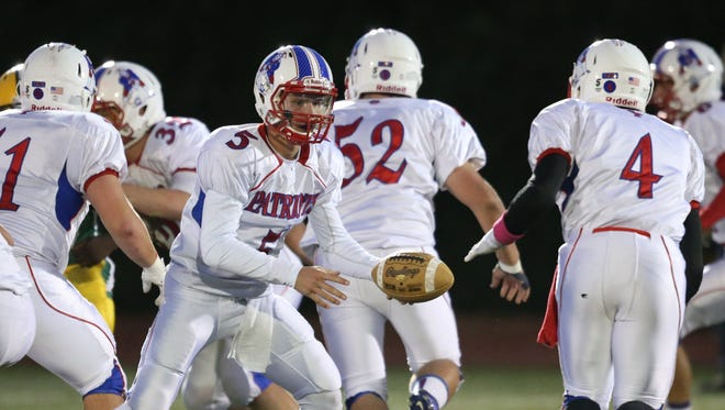 Cousino high schools  Nick Palmer hands off to Steven Charles Jr during first half action Friday, October 10, 2014 at Grosse Point North.