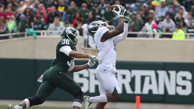 Michigan State's Arjen Colquhoun is late on the defense as Montae Nicholson catches the football near the sidelines during the Michigan State Spartans annual spring football game at Spartan Stadium in East Lansing, Michigan on Saturday, April 25, 2015. The White team beat the Green team, 9-3.