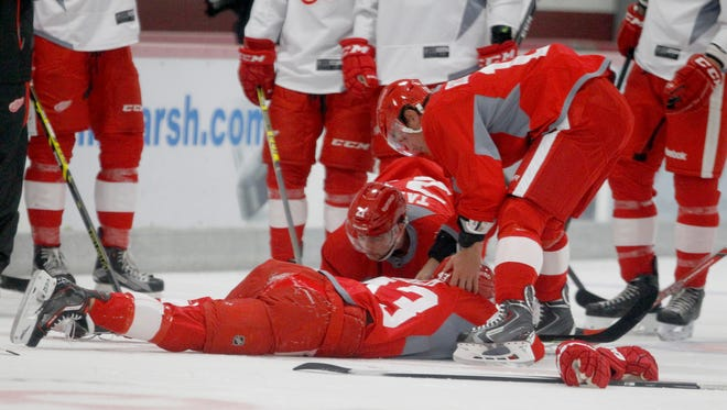The Red Wings' Darren Helm is checked on by teammates after his collision with Jerome Verrier on the first day of training camp.