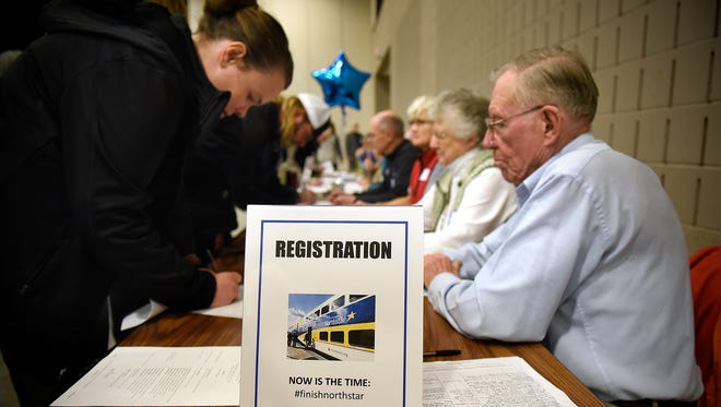 People sign in before the start of the GRIP/ISAIAH event at the River's Edge Convention Center in support of extending the Northstar Commuter Rail line to St. Cloud.
